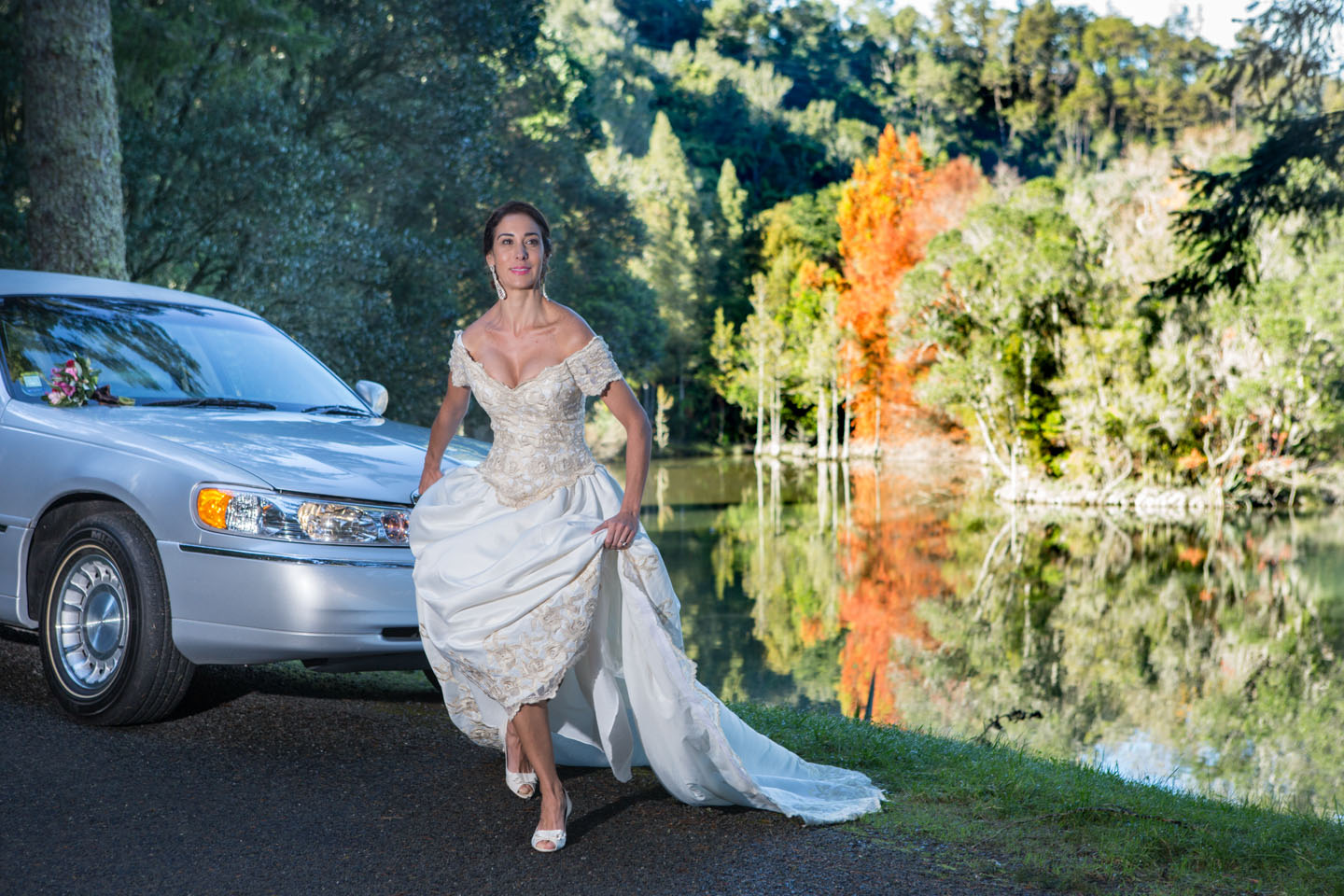 bride about to run at McLaren Falls Park with a limousine in the background