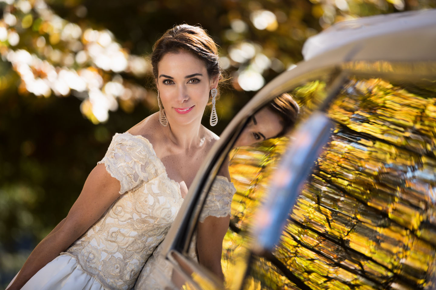 bride with the refection of autumn leaves in the window of a limousine