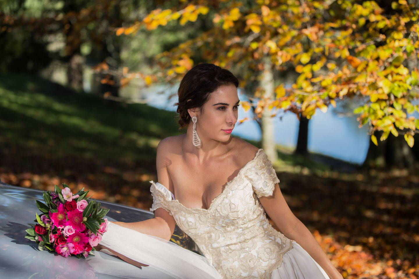 bride looking to her left with autumn leaves and water in the background