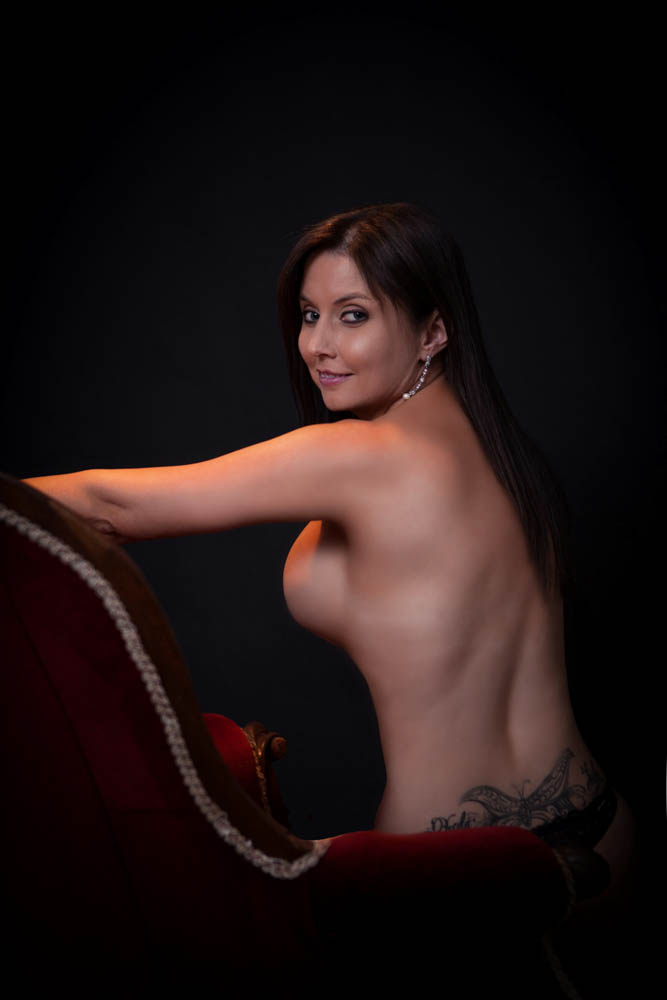 boudoir image of a beautiful women with a red velvet chair