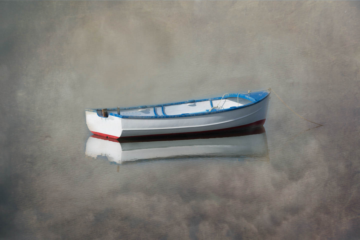 dingy floating on a still sea with the sky and clouds reflecting in the water