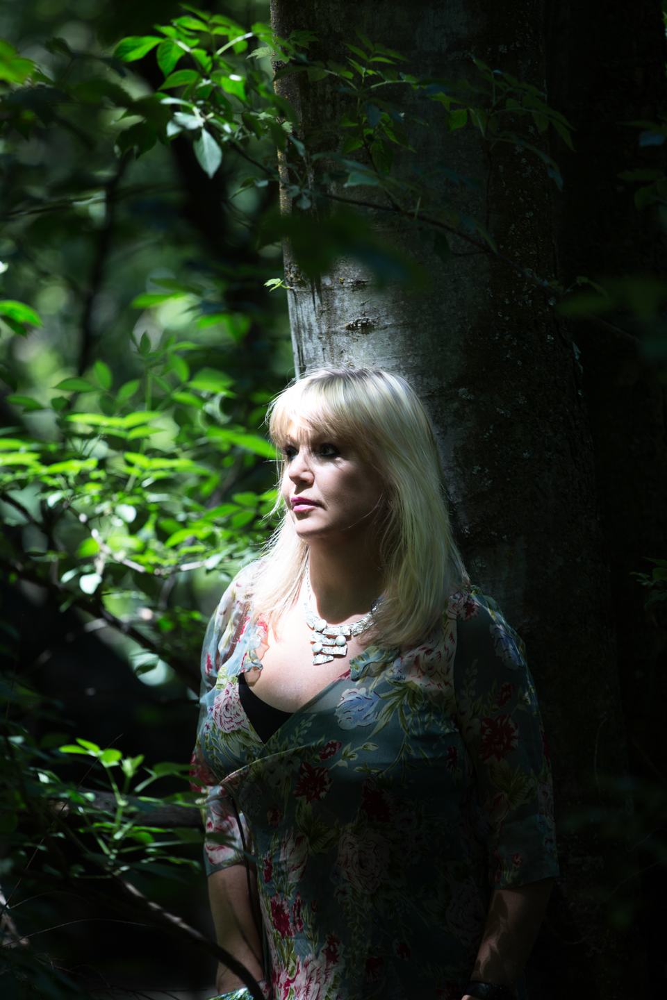Jackie Brown in the forest with natural sunlight on her face in Arrowtown