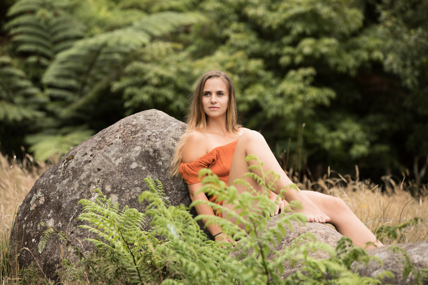 gorgeous women in a orange top leaning against a rock