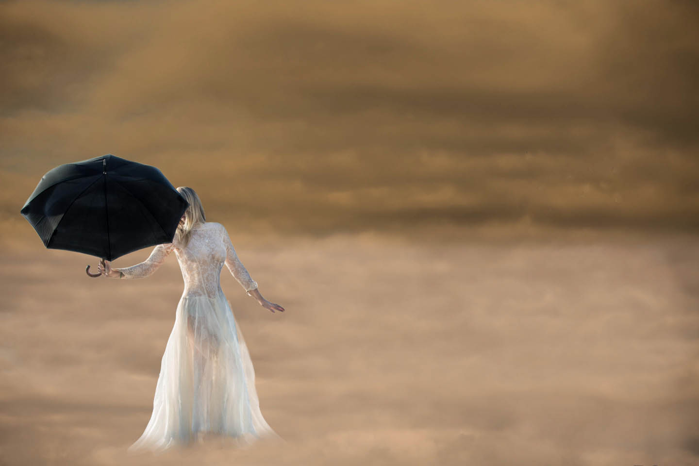 bride holding a black umbrella floating in the clouds