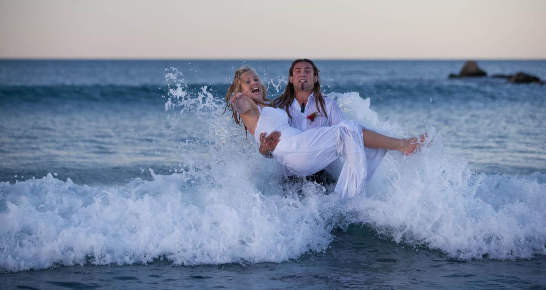 a wave hitting a bridal couple at Mount Maunganui