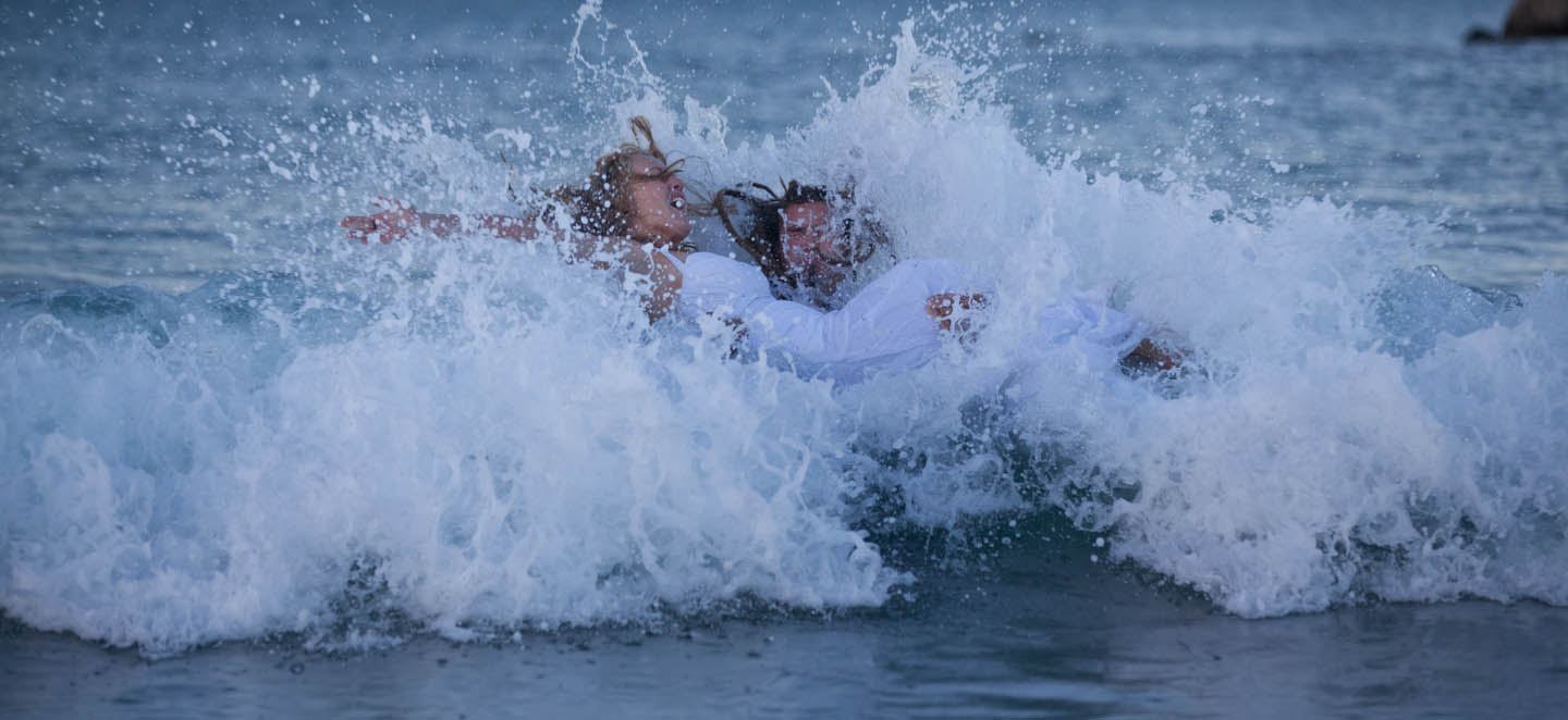 bride and groom falling in the breakers at Mount Maunganui