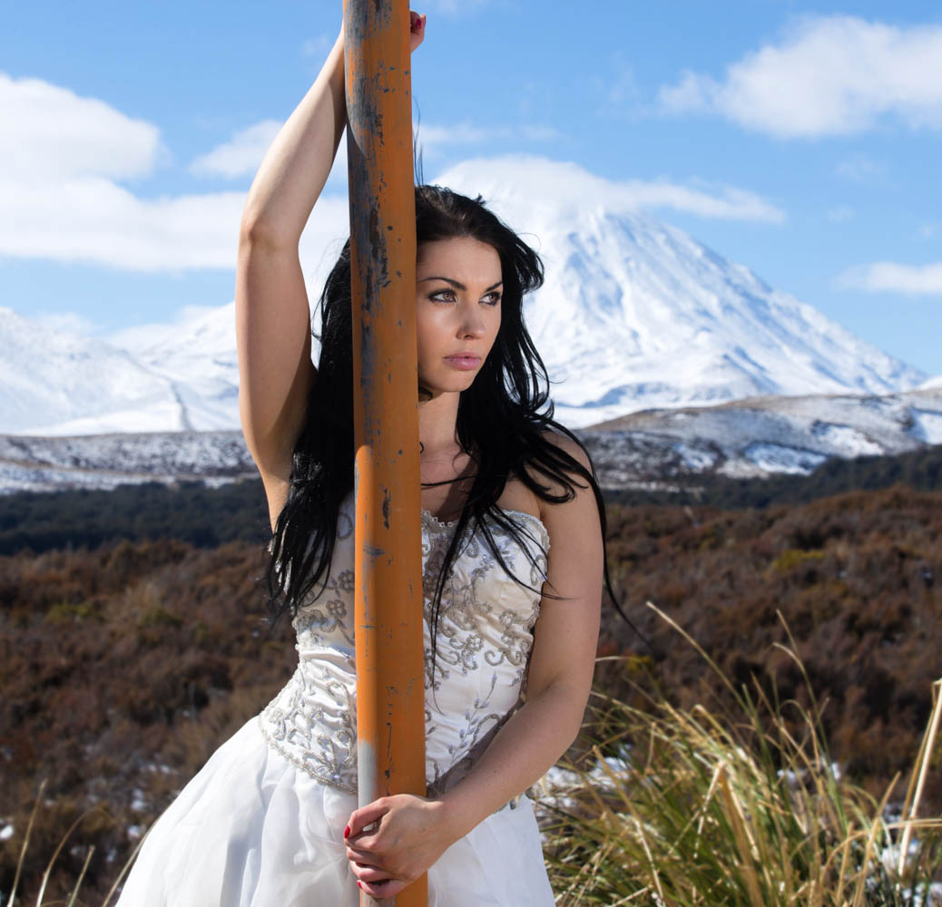 beautiful bride leans against a pole with Mount Ngauruhoe in the backgrounder