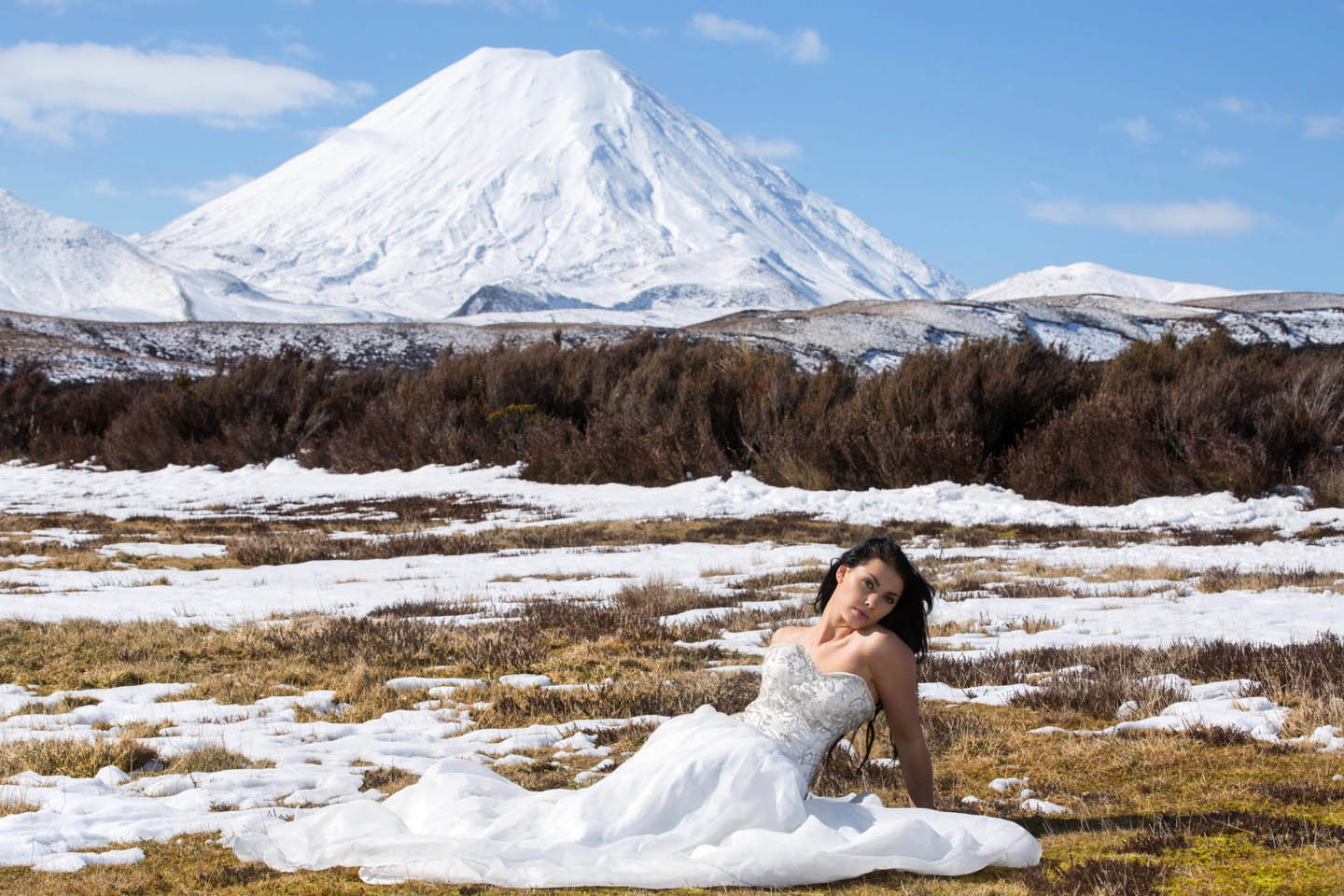 bride sitting in the snow with Mount Ngauruhoe as a backdrop