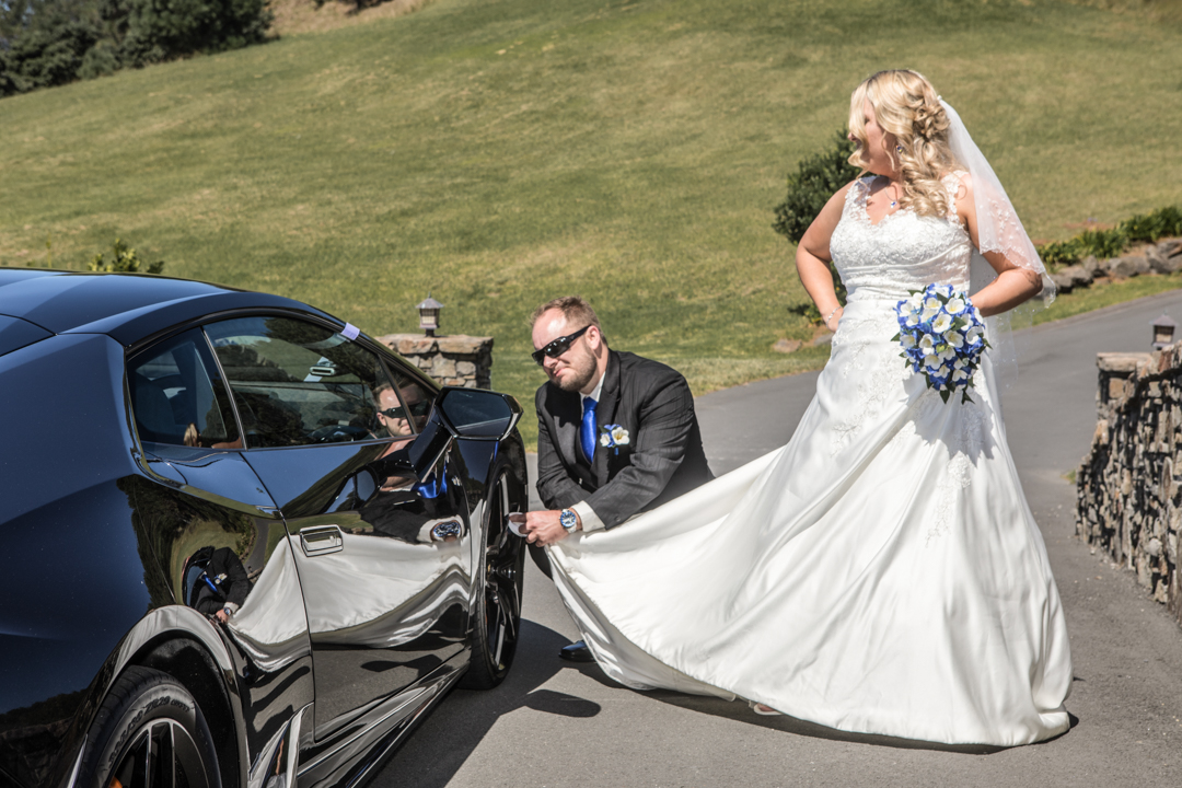 groom cleaning th wheels of a Lamborghini with his wife's wedding dress
