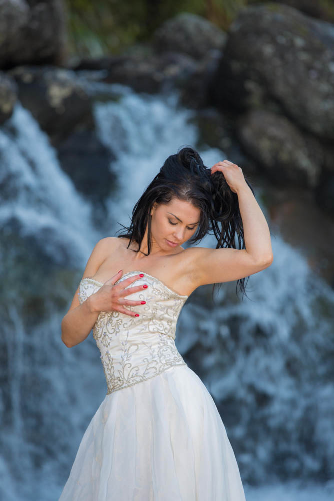 bride clutching her chest standing in front of a waterfall