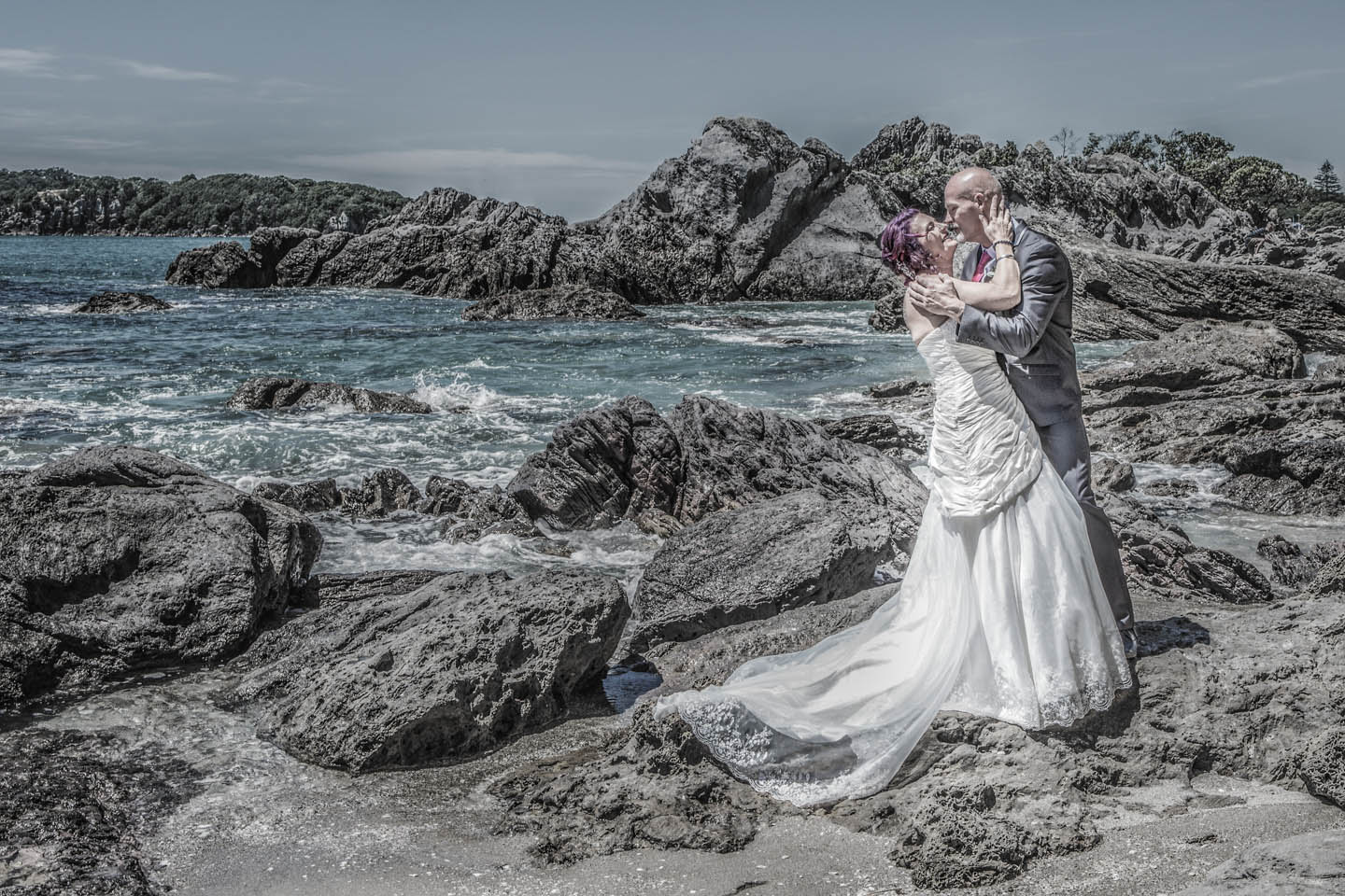 dramatic photo of a bride and groom standing on the rocks at Mount Maunganui