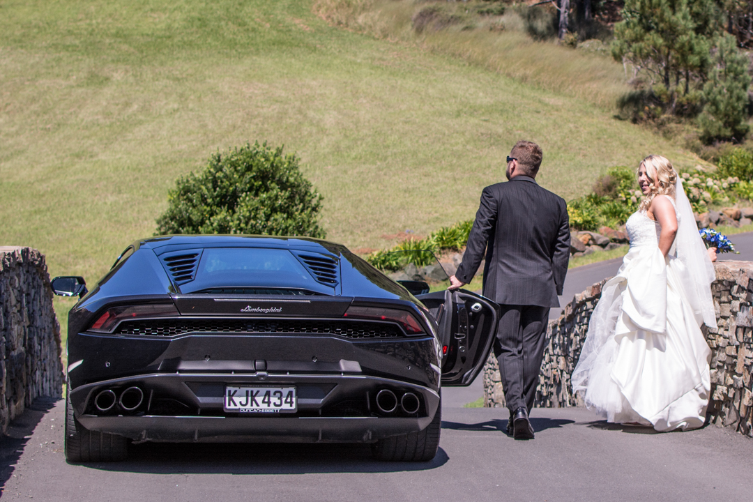 Groom taking his bride and Lamborghini for a walk at the Leadfoot Ranch Wedding venue in Hahei