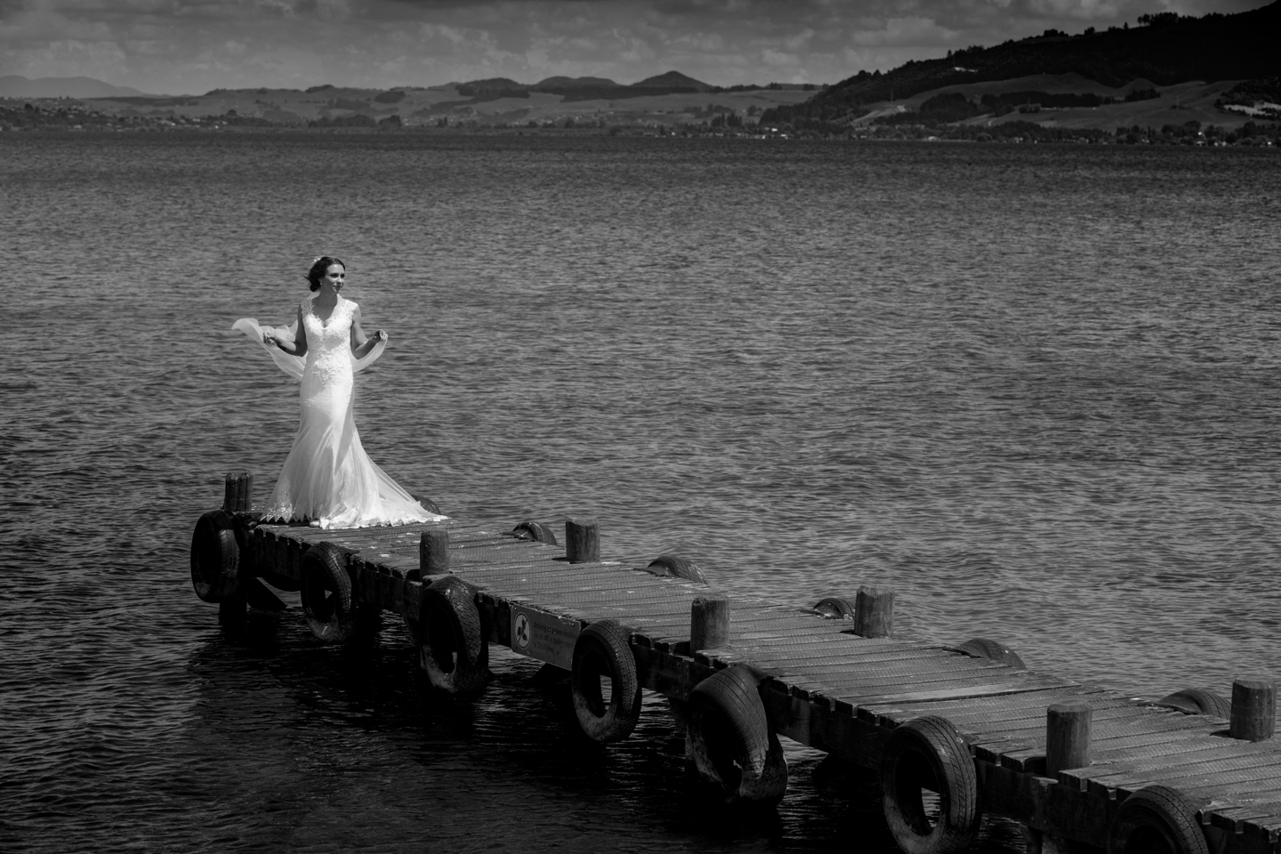 black and white image of a bride on the end of a jetty waving her veil in Rotorua