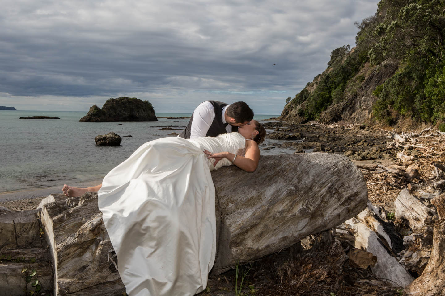 groom passionately kisses his bride while she is laying on a large driftwood tree at Whakatane beach