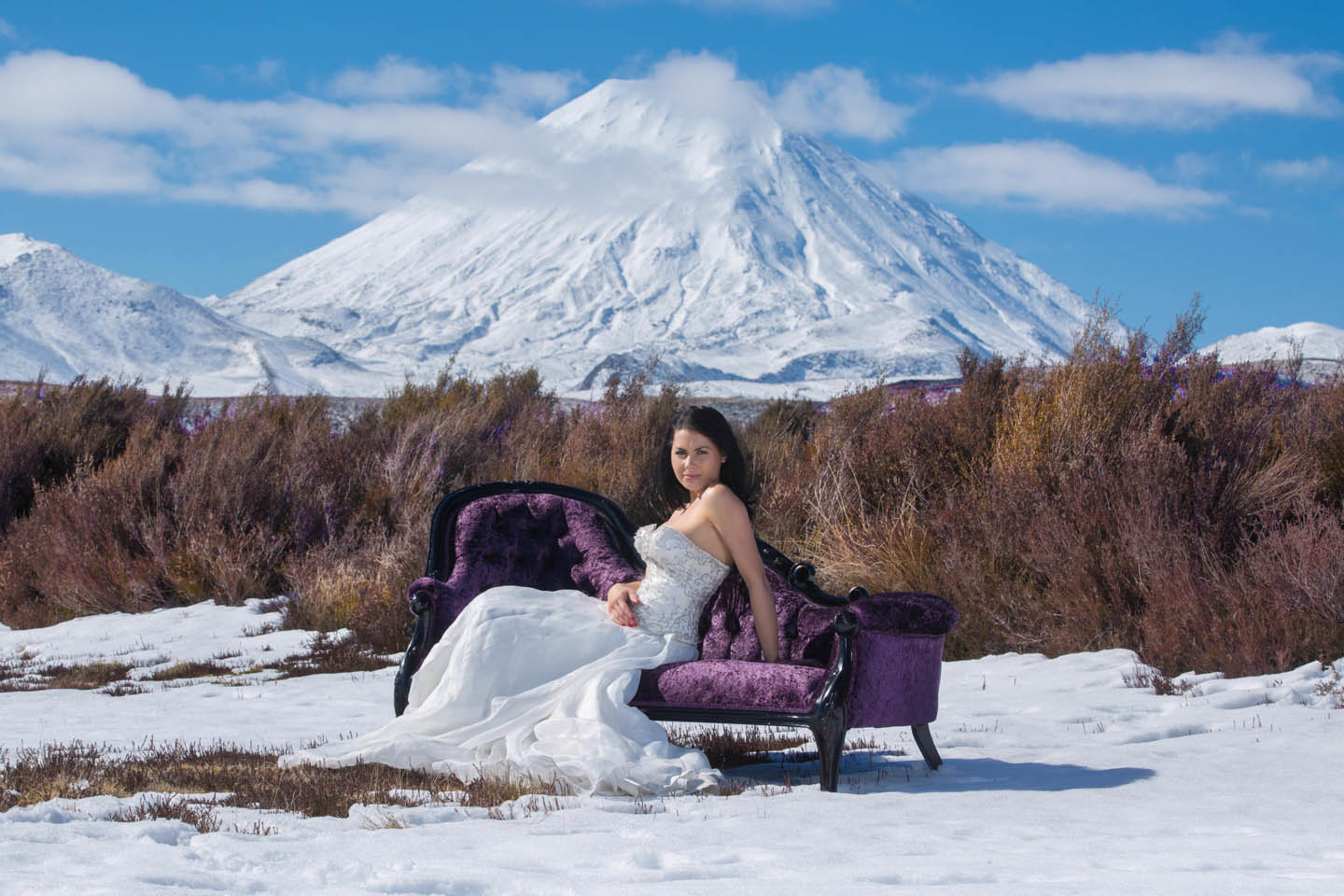 bride sitting on a purple chase lounge in the wilderness in the snow