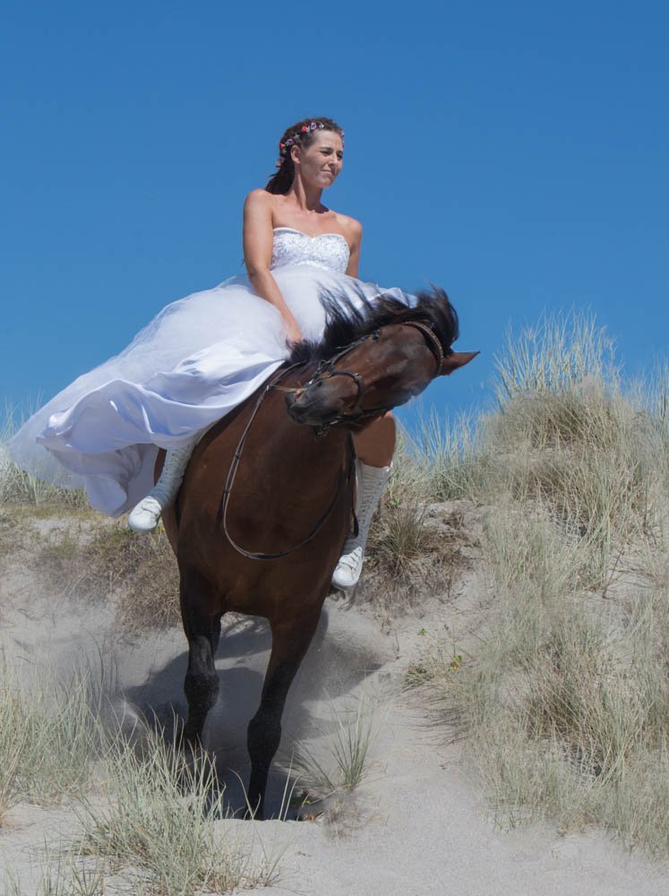 bride riding down the sand dunes at Papamoa Beach