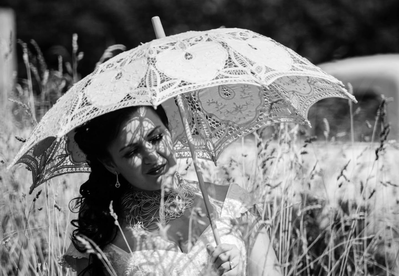 bride holding a lace parasol at Eagle Ridge Estate