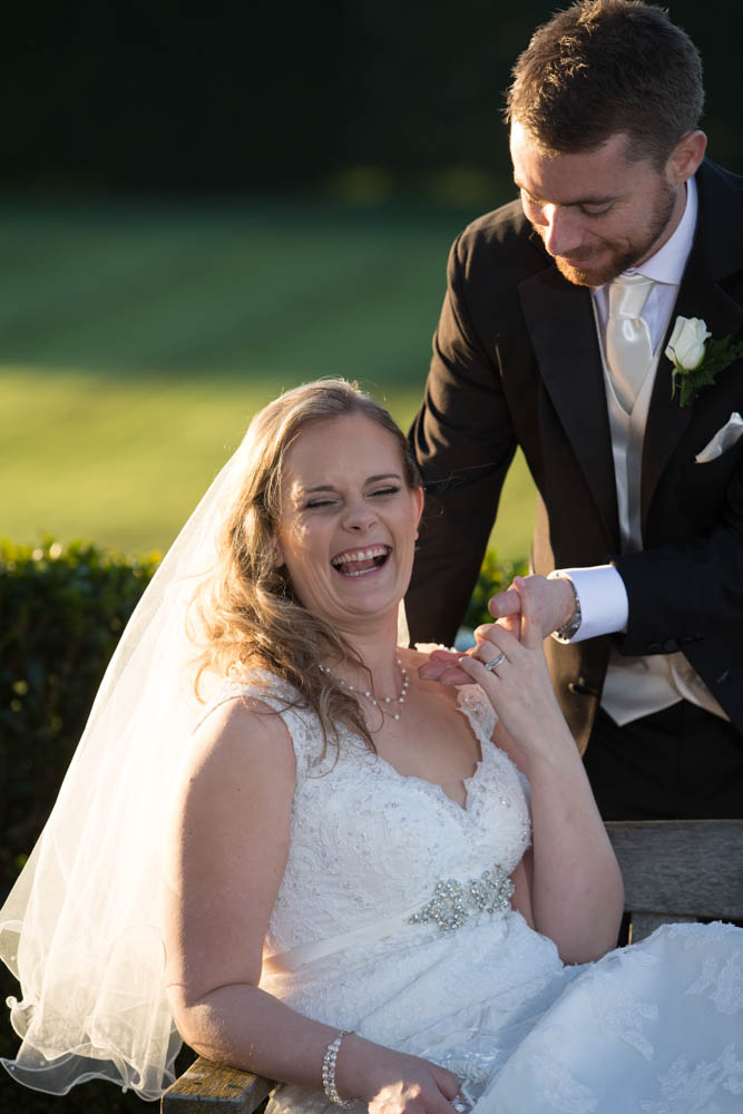 laughing bride with her husbands hand on her shoulder