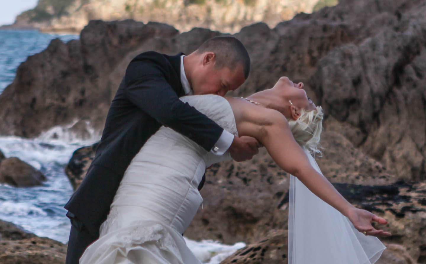 dramatic photo of a groom kissing the brides chest on the rocks at Mount Maunganui