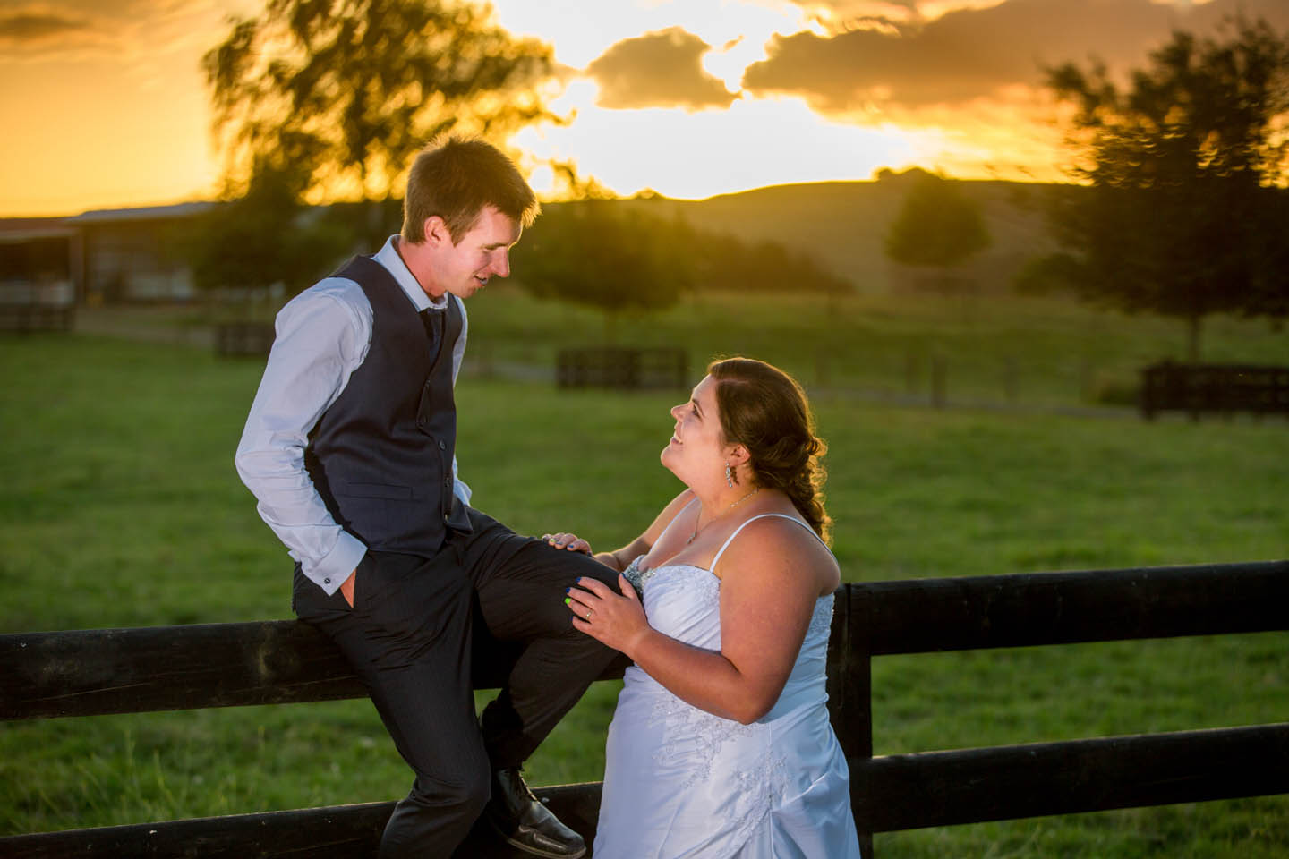 groom sitting on a fence talking to his bride at The Red Barn at sunset