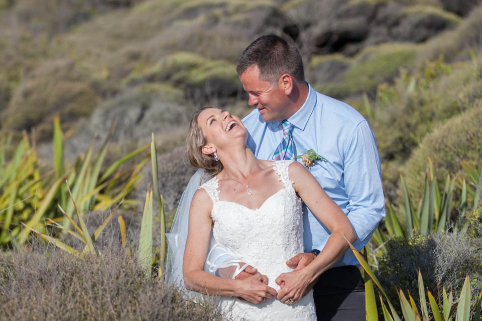 bride and groom laughing amongst coastal scrublands in Opononi
