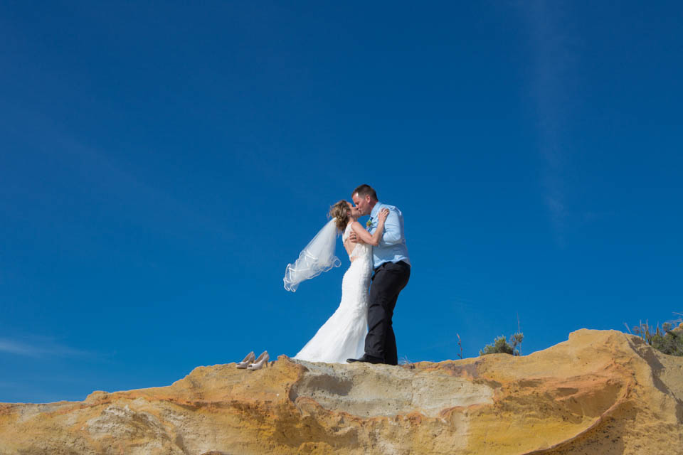 bride and groom embrace and kiss on top of a cliff under clear blue skies