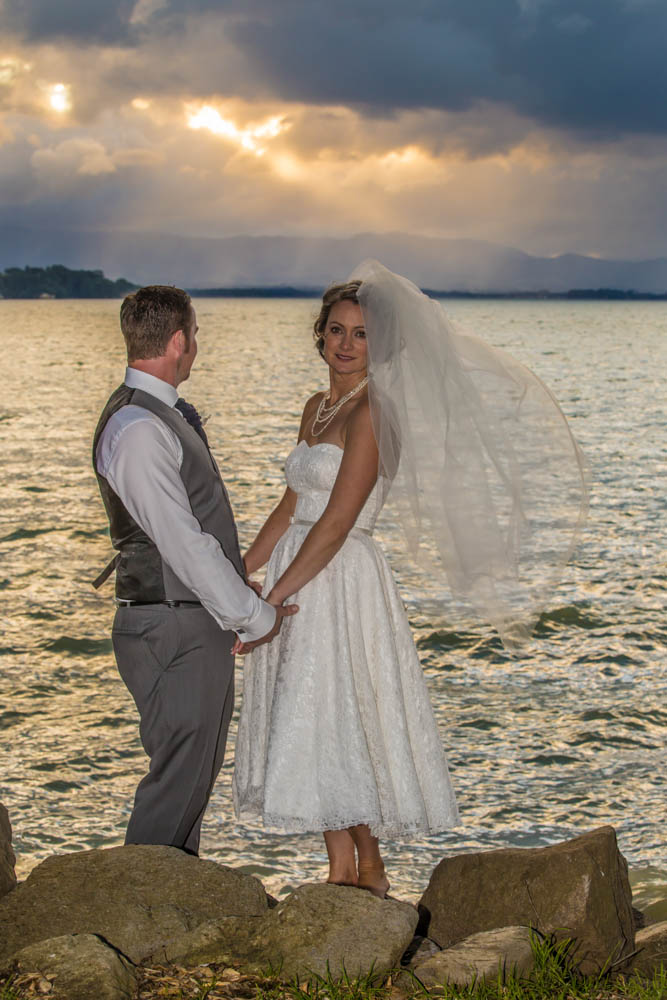 bride and groom standing by the waters edge in Omokoroa