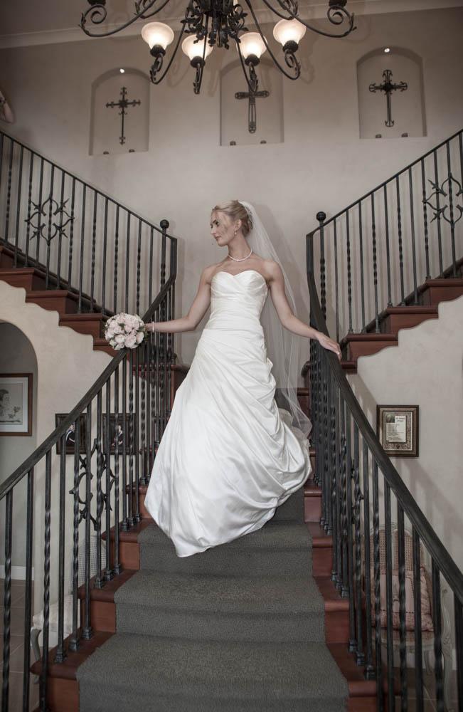 bride descends beautiful staircase in Omokoroa