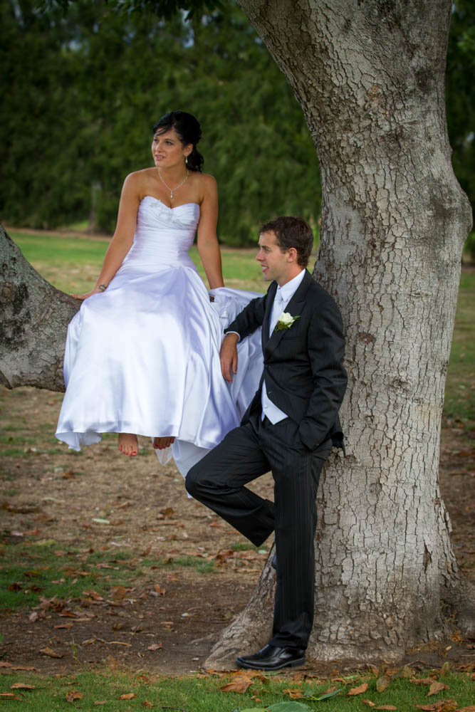 bride sitting on a branch of the tree that her husband is standing beside