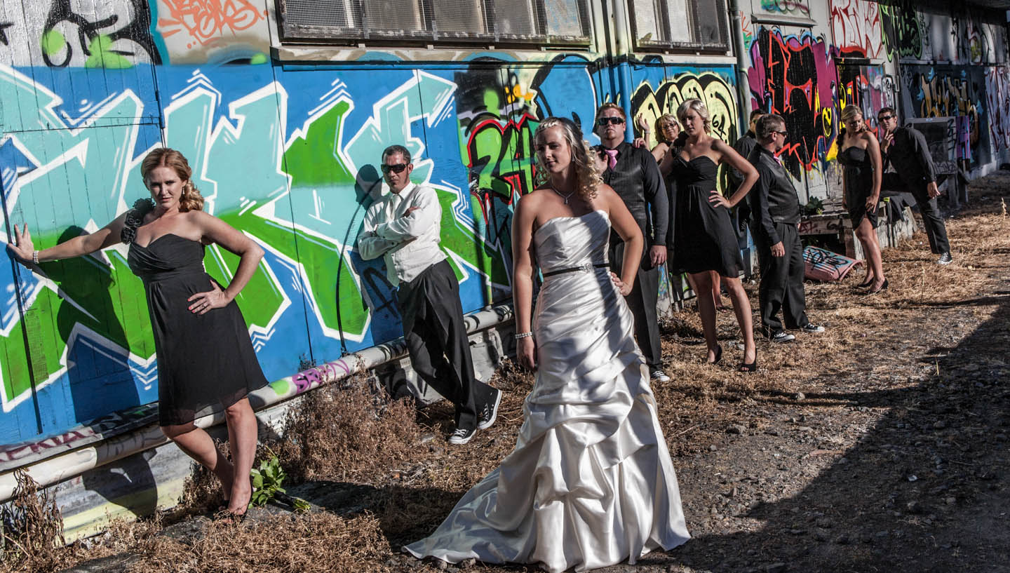 bridal party in front of a graffiti wall in Tauranga