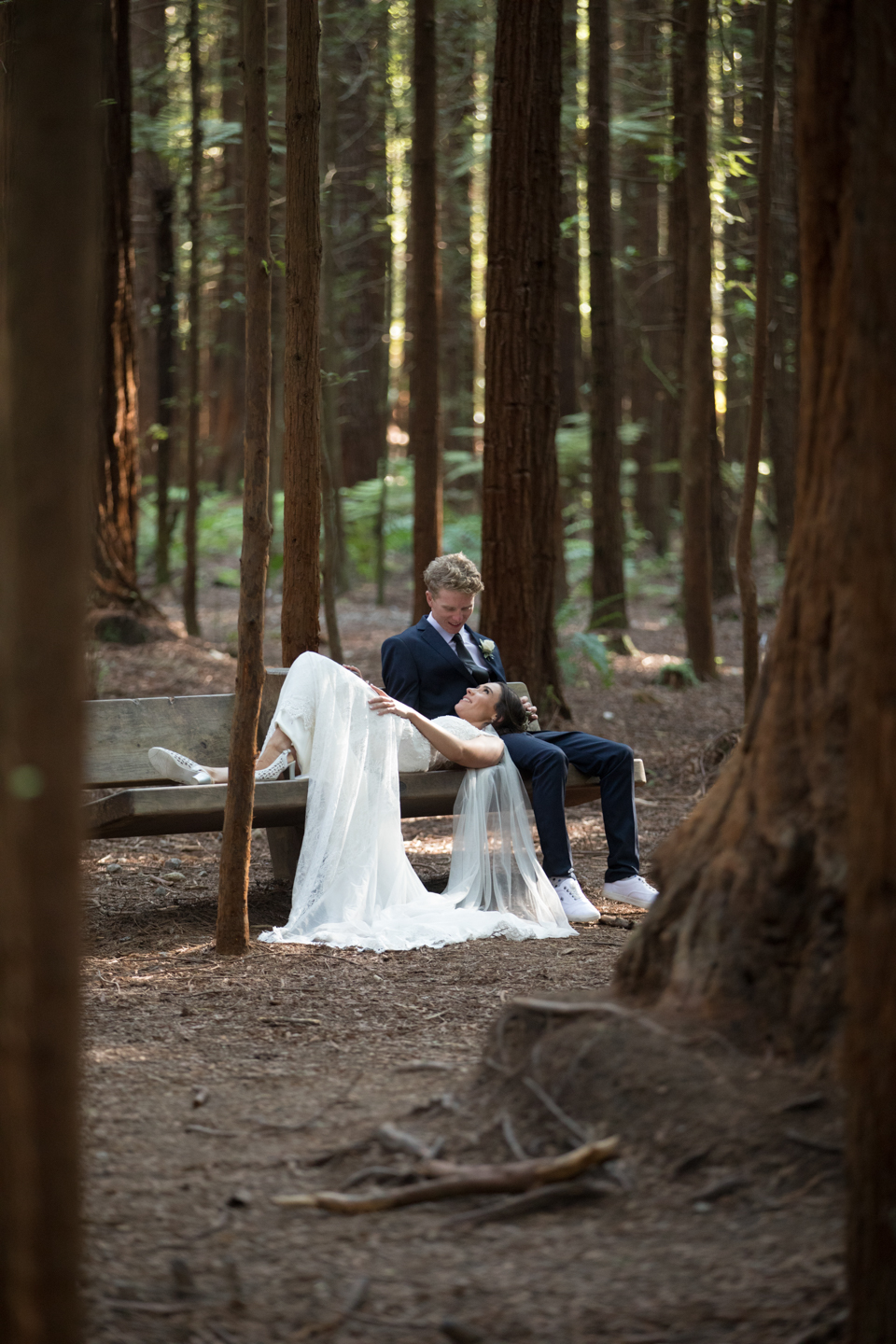 bride lying on a park bench with her head in her husbands lap at the Redwoods in Rotorua