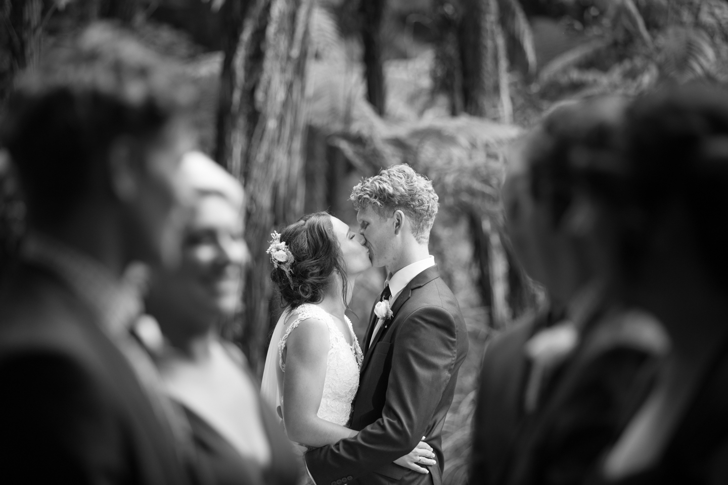 black and white of a bridal couple with their bridal party in the foreground