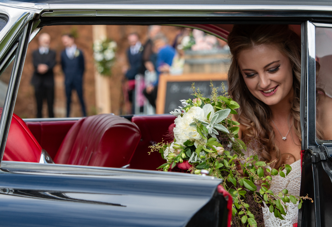 Bride getting out of her car with groom in the background