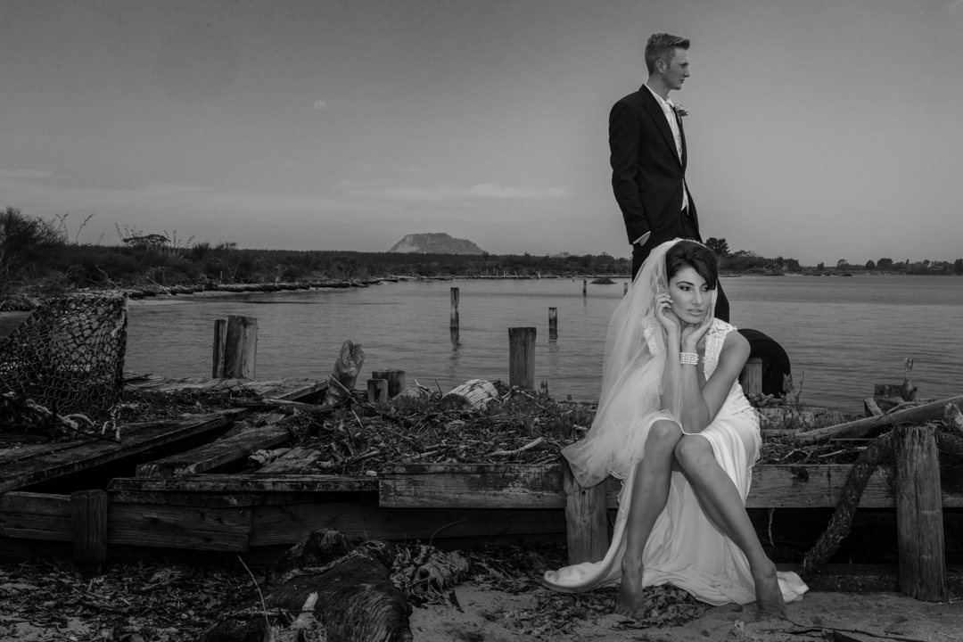 Black and White image of a Bride and groom on a old jetty