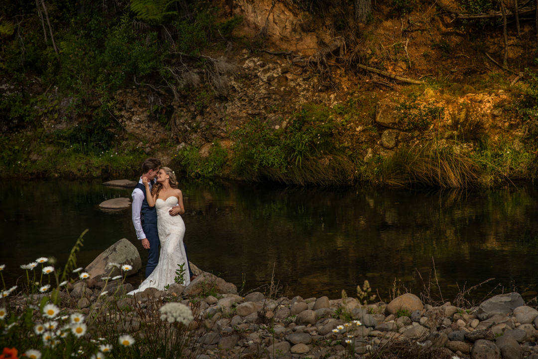 bride kissing groom by the river
